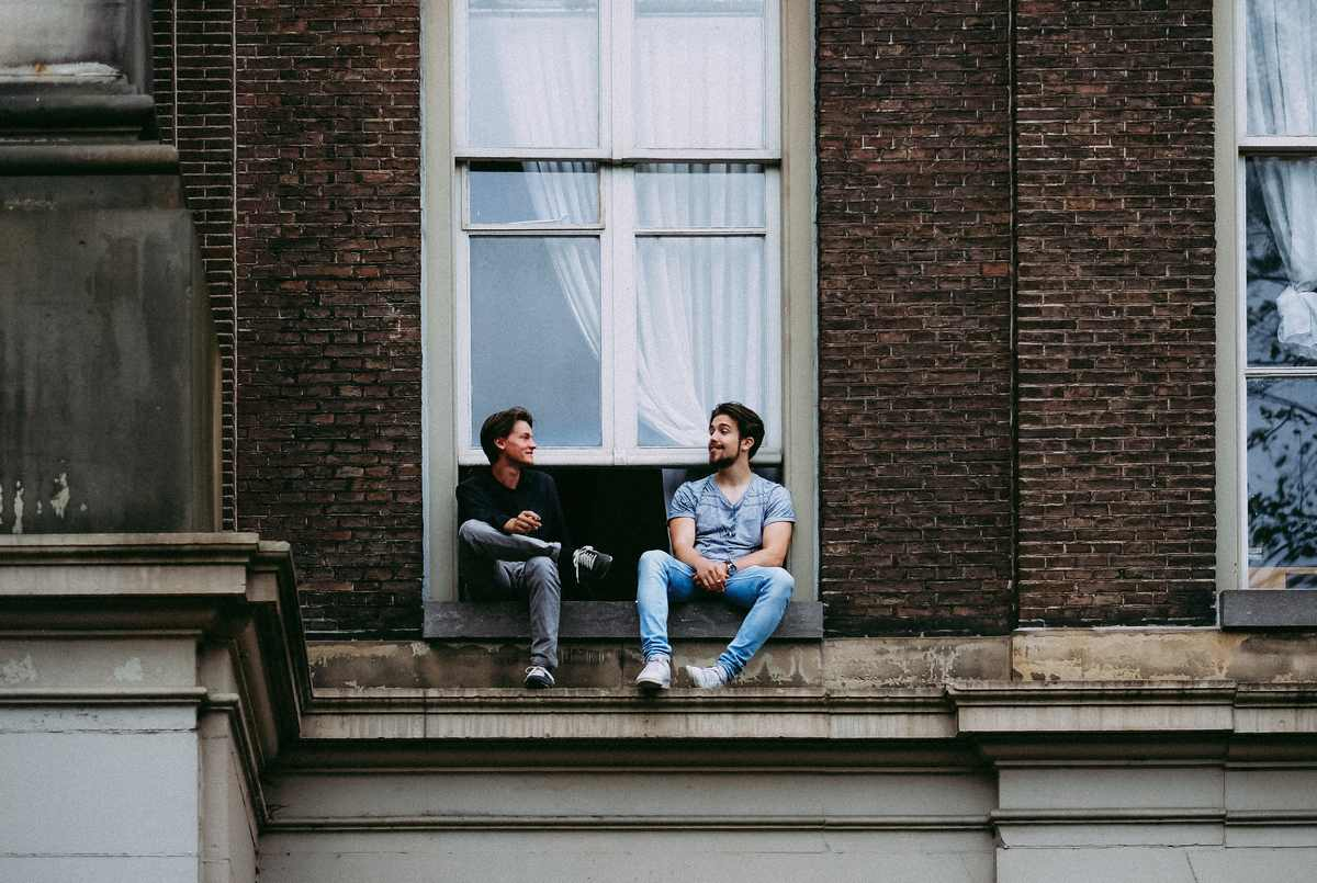 Men sitting on windowsill. Photo by Wenni Zhou on Unsplash